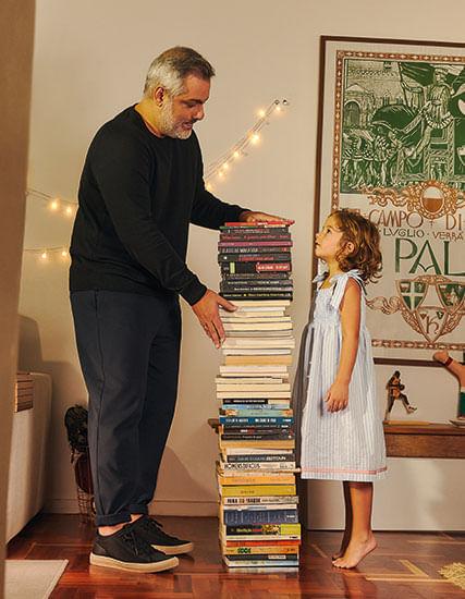 Foto - Pai André com filha ao lado de pilha de livros